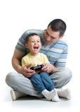 Barnet och hans fader spelar med en playstation tillsammans Royaltyfria Foton
