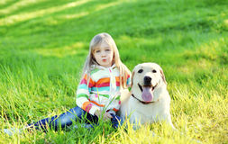Barnet och labrador retriever dog sammanträde på gräs i sommar royaltyfria foton
