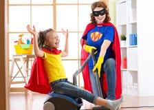 Barnet och mamman klädde som superheroes som använder dammsugare i rum Familj - kvinna- och ungedottern har en gyckel medan royaltyfria foton