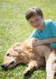 Barnet omfamnar lovingly hans älsklings- hund Arkivfoton
