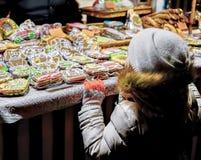 Barnet på färgrika pepparkakor på den Riga julen marknadsför Royaltyfri Bild