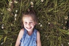Barnet på grönt tusenskönagräs i en sommar parkerar solnedgångtid royaltyfri fotografi