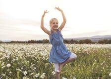 Barnet på grönt tusenskönagräs i en sommar parkerar solnedgångtid som gör balerina fotografering för bildbyråer