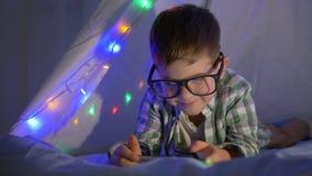 Barnet på natten med mobiltelefonen ligger i vigvammet som dekoreras med en hemmastadd närbild för girland arkivfilmer