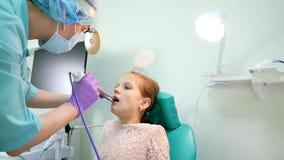 Barnet på otolaryngologymottagandet, den Lor doktorn behandlar ett sjukt barn, apparaturen för behandling av angina, behandling a stock video