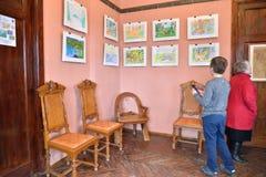Barnet på utställningen av barns teckningar i museet Arkivbilder