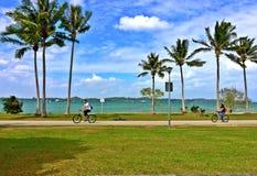 Barnet par somridningen cyklar på en strand, parkerar Arkivfoto