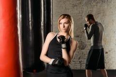 Barnet passade den blonda damen i boxninghandskar som får klara för utbildning i idrottshallen, idrotts- blond grabbboxning bak h Arkivfoto