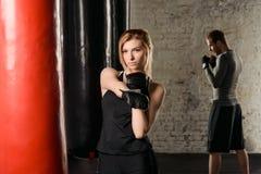 Barnet passade den blonda damen, i sträckning för boxninghandskar som får klar för utbildning i idrottshallen Royaltyfri Foto