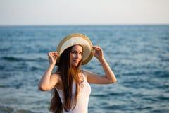 Barnet passade kvinnan i sommardräkt och bärande hatt vid sjösidan Royaltyfria Foton