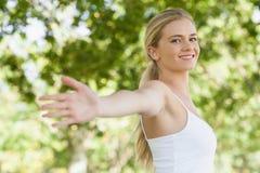 Barnet passade kvinnan som gör yoga i en parkera som fördelar henne armar Arkivbild