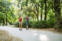 Barnet passade kvinnor som utomhus joggar Arkivfoto