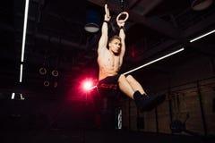 Barnet passade mannen som drar upp på gymnastiska cirklar Royaltyfria Foton