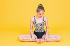 Barnet passar kvinnan som gymnasten som sträcker i lotusblomma, poserar Arkivbild