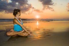 Barnet passar och kondition och yoga för sund attraktiv kvinna praktiserande i härlig solnedgångstrand i meditation och avkopplin royaltyfria bilder