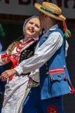 Barnet polerar dansare i traditionell dräkt Arkivbild