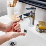 Barnet räcker att skumma med tvål med skönhettillbehör på vask Royaltyfri Bild
