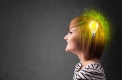 Barnet är besvärad att tänka av grön ecoenergi med lightbulben Arkivfoto