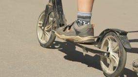 Barnet rider en sparkcykel i en sommar parkerar Närbild lager videofilmer