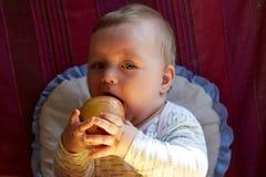 Barnet rymmer äpplet i hand Royaltyfria Foton