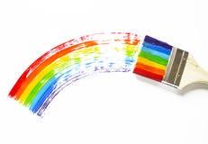 Barnet rymmer borsten Ungen målar en lönnlöv målade sammanlagt färgerna av regnbågen Mångfärgad båge arkivfoton