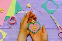 Barnet rymmer en hjärtahängehalsband i hans händer Barnet gjorde en hjärtahängehalsband från filt, pryder med pärlor och knäppas  Royaltyfria Bilder