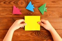 Barnet rymmer en pappers- fyrkant i hans händer Fisk för barndanandeorigami Uppsättningen av origami fiskar på en trätabell Royaltyfri Fotografi