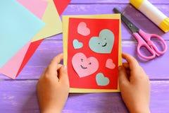 Barnet rymmer ett valentinhälsningkort i hans händer Barnet är uppvisning valentin hälsningkortet Enkla pappers- hantverk fotografering för bildbyråer