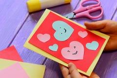 Barnet rymmer ett valentinkort i hans händer Barnet visar ett hälsningkort lyckliga valentiner för kortdag Lätta pappers- hantver Royaltyfri Bild