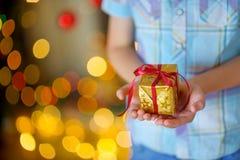Barnet rymmer försiktigt i handen en julgåva Fotografering för Bildbyråer