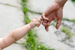 Barnet rymmer fingret av en hand Arkivbild