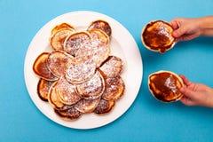 Barnet rymmer i hans händer två hemlagade frasiga ovala pannkakor fotografering för bildbyråer