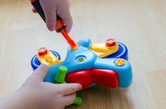 Barnet samlar en leksakmotorcykel Arkivbild