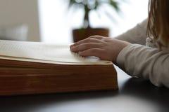 Barnet satte hans händer på boken och läste den Arkivbild