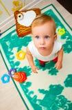 Barnet ser in i kameralinsen Barn som spelar med den bildande färgpyramidleksaken Royaltyfri Foto