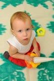Barnet ser in i kameralinsen Barn som spelar med den bildande färgpyramidleksaken Royaltyfria Bilder