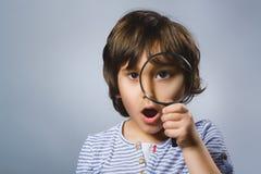 Barnet ser igenom förstoringsglaset, ungeögat som ser med förstoringsapparaten Lens över grå färger royaltyfria foton
