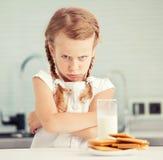 Barnet ser med avsmak för mat royaltyfria foton
