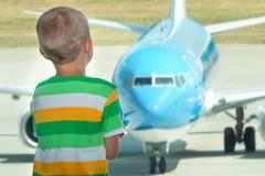 Barnet ser nivån till och med fönstret av flygplatsen royaltyfria foton