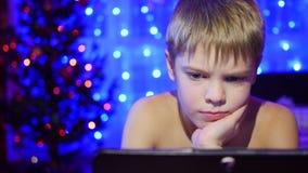 Barnet ser till minnestavlan som ligger på säng bakgrunden tänder girlander Royaltyfri Fotografi