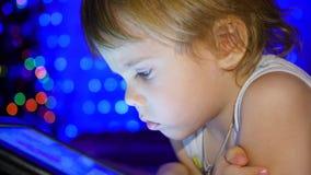 Barnet ser till minnestavlan som ligger på säng I bakgrunden, ljusen och girlanderna av julgran Royaltyfri Fotografi