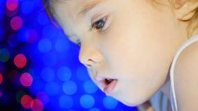 Barnet ser till minnestavlan som ligger på säng I bakgrunden, ljusen och girlanderna av julgran closeup Arkivfoton