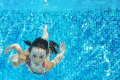 Barnet simmar i den undervattens- pölen, den lyckliga aktiva flickan dyker och har gyckel under vatten, ungekondition och sport Fotografering för Bildbyråer