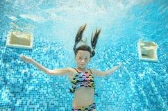 Barnet simmar i den undervattens- pölen, den lyckliga aktiva flickan dyker och har gyckel under vatten, ungesport arkivbilder