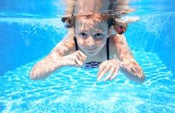 Barnet simmar i den undervattens- pölen, den lyckliga aktiva flickan har gyckel royaltyfria foton