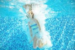 Barnet simmar i den undervattens- pölen, den lyckliga aktiva flickan hoppar, dykar och har gyckel under vatten, lurar kondition o Royaltyfria Bilder