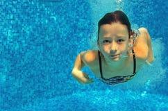 Barnet simmar i den undervattens- pölen, den lyckliga aktiva flickan hoppar, dykar och har gyckel, ungesport arkivbilder