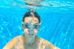 Barnet simmar i den undervattens- pölen, den roliga lyckliga flickan i skyddsglasögon har gyckel under vatten och gör bubblor, un Arkivfoto