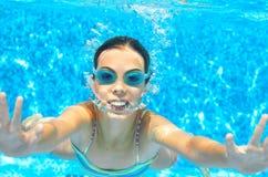 Barnet simmar i den undervattens- pölen, den roliga lyckliga flickan i skyddsglasögon har gyckel under vatten och gör bubblor, un royaltyfria foton
