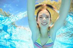 Barnet simmar i den undervattens- pölen, flicka har gyckel i vatten arkivbilder